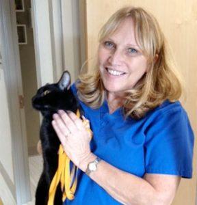Team member Dr. Caroline Chamarande holding a black cat